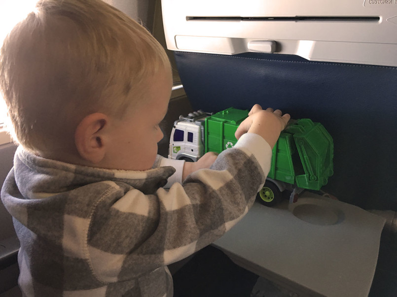 """Playing with his """"baby"""" recycling truck on the flight to Boston."""